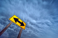 Storm Over Yellow Double Arrow Road Sign