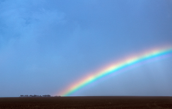 Rainbow at Twilight Over Rural Landscape
