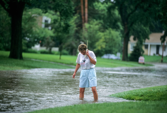 Woman Talking On Vintage Cordless Phone While Standing In Flooded Street