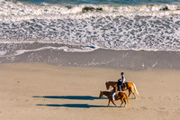 Couple Riding Horseback on Beach